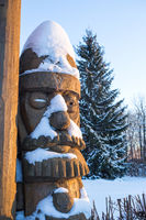 Wooden sculpture of fairy-tale character covered with snow at sunset