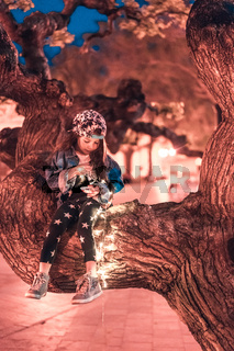 preschool girl sitting on a tree branch