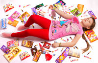 The girl lies strewn with sweets and other sweets of famous brands...
