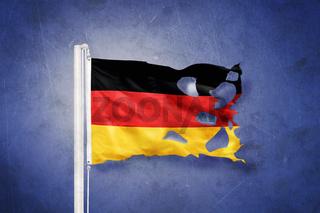 Torn flag of Germany flying against grunge background