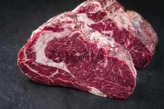 Two Raw dry aged Kobe rib eye Steak as close-up on a black board