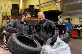 auto mechanics changing car tires at workshop