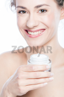 Young woman holding a moisturizer jar in her hands.