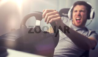 close up of man playing car racing video game