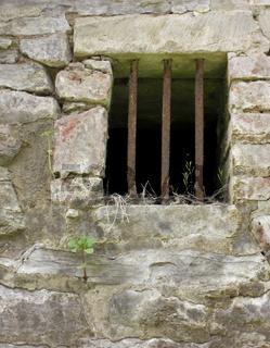 Gitterstäbe in einer alten Bruchsteinmauer