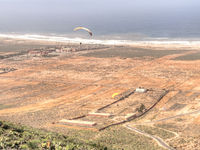 Two paragliders flying over a coastal plain