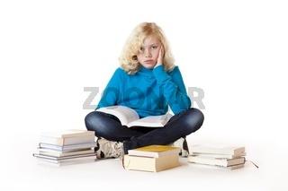 Schulmädchen sitzt frustriert am Boden und versucht zu lernen
