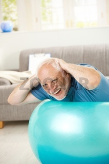 Happy active senior exercises on fit ball
