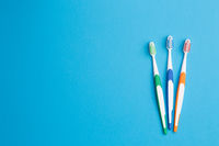 Three toothbrushes on blue background