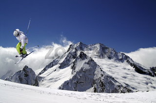 Skier jump with crossed skis in high snowy mountains