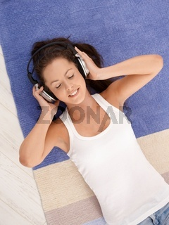 Attractive girl laying on floor enjoying music