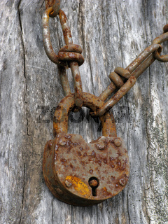 Closeup of an old padlock and rusty chain