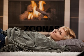 Woman resting beside fireplace