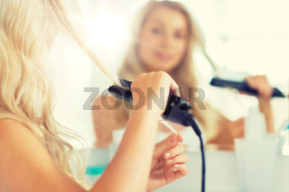 woman with styling iron straightening hair at home