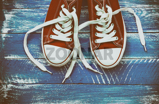 pair of red sneakers on a blue shabby wooden surface