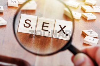 concept image of a magnifying glass zoom on a word SEX placed on a desk in precious wood
