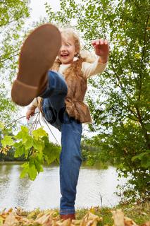 Kind tobt im Herbst im Freien