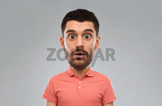 surprised man in polo t-shirt over gray background