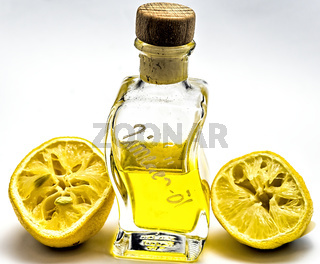 Bottle with lemon oil and two squeezed lemon halves against a white background