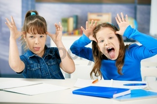 Children sticking tongue in classroom