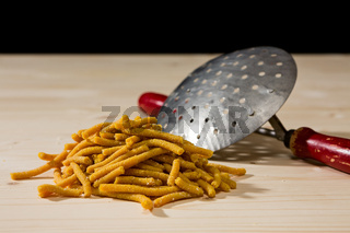 Passatelli original Italian pasta over a wooden background