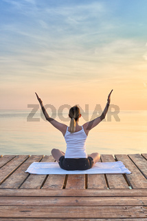 Young woman practicing yoga by sea