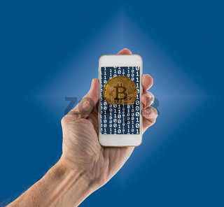 Bitcoins emerging from app on handheld smartphone