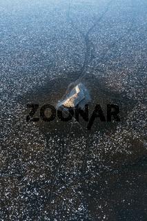 Stein in einem gefrorenen See, Lappland