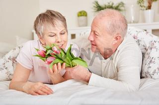Senior überrascht seine Frau mit Blumen