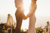 The bride and groom on the background of the Ocean during sunset