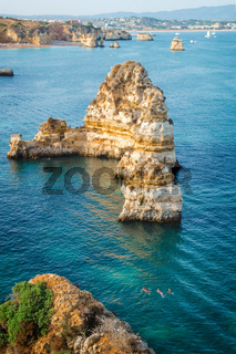 People swimming in the sea on the shoreline of Lagos coasts, Algarve, Portugal.
