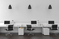 Work desks in empty room with big wall in background