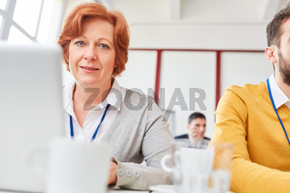 Ältere Geschäftsfrau in Computer Schulung