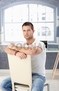 Young man in jeans sitting conversely on chair