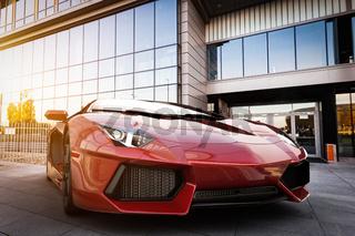 Red fast sports car in modern urban setting. Generic, brandless design