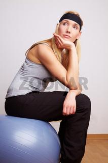 Frau sitzt auf Gymnastikball