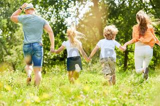 Aktive Familie und Kinder laufen über Wiese