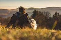Mann blickt gemeinsam mit seinem Hund in die Ferne