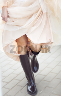 Bride wearing rubber boots outside