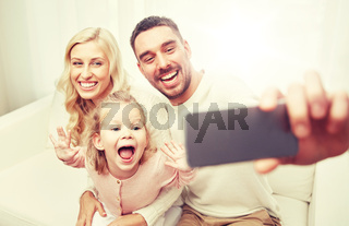 family taking selfie with smartphone at home