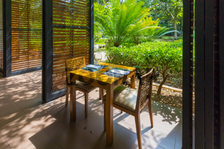 restaurant table set overlooking tropical garden