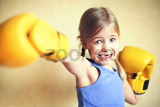 Little girl with yellow boxing gloves over yellow wall background. Girl power concept. Funny little kid portrait.