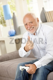 Older man giving thumb up with computer game