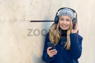 Frau mit Kopfhörern und Smartphone