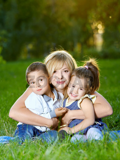 Mother embraces two children on a summer lawn