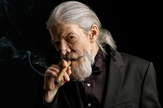Stylish aged man with long grey hair smoking cigar.