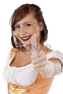 Junge, hübsche, bayerische Frau im Dirndl zeigt Daumen nach oben