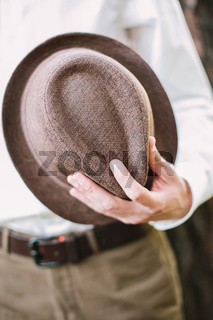 the man holds a trilby hat in hand.