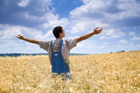 farmer in wheat field with arms spread out