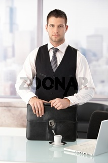 Young businessman standing at desk in office